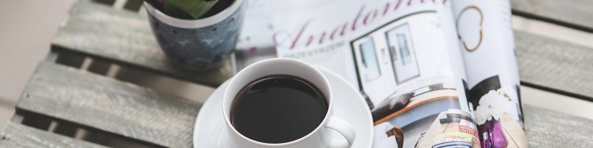 Et bord med en blomst, en avis og en kop kaffe