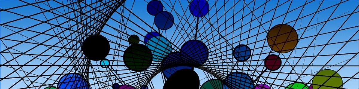 Et net udspænde op mod den blå himmel med påsatte glascirkler i strplende farver
