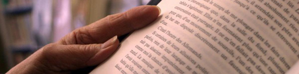 Nærbillede af tekst i bog og en hånd der holder bogen