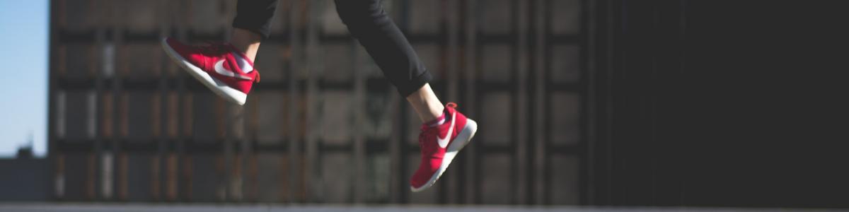 Billedet viser den nederste del af et ungt mennesket der hopper højt op en gade.