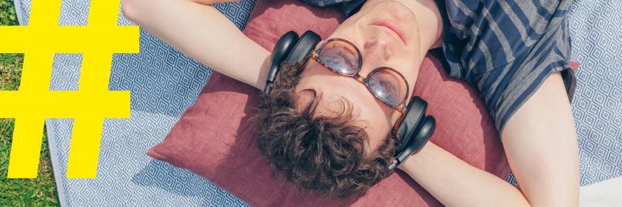 Billedet af en mands hoved tage ovenfra. Manden ligger med armene bag hovedet og lytter til en lydbog gennem sine hørebøffer. På venstre hånd står der en gul hashtag.