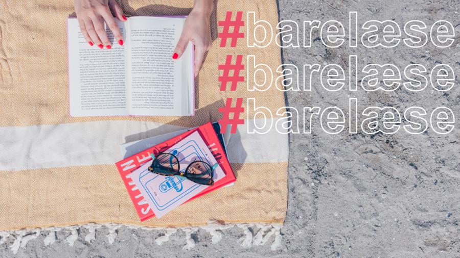 Billedet taget ovenfra af sand, et badehåndklæde på sanden med to bøger på og en åben bog hvorpå to hænder ligger. På venstre hånd står der hashtag barelæse tre gang.