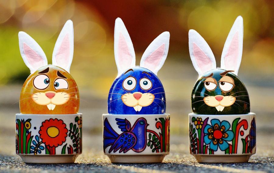 Billedet viser tre kopper med påskeæg i. Æggene er klædt på som kaniner.