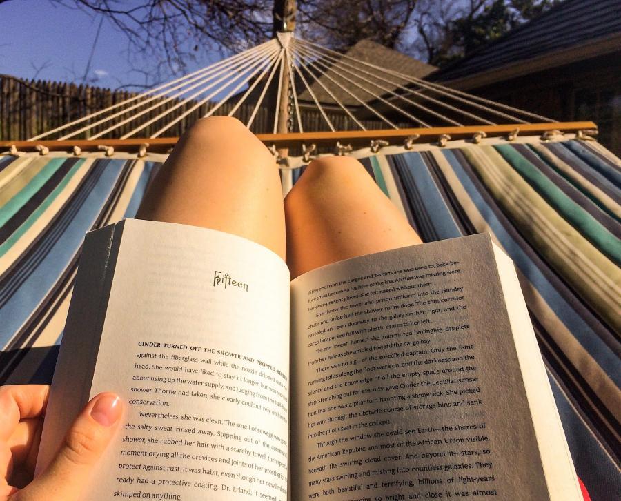 En bog hviler på benene af en person i en hængekøje