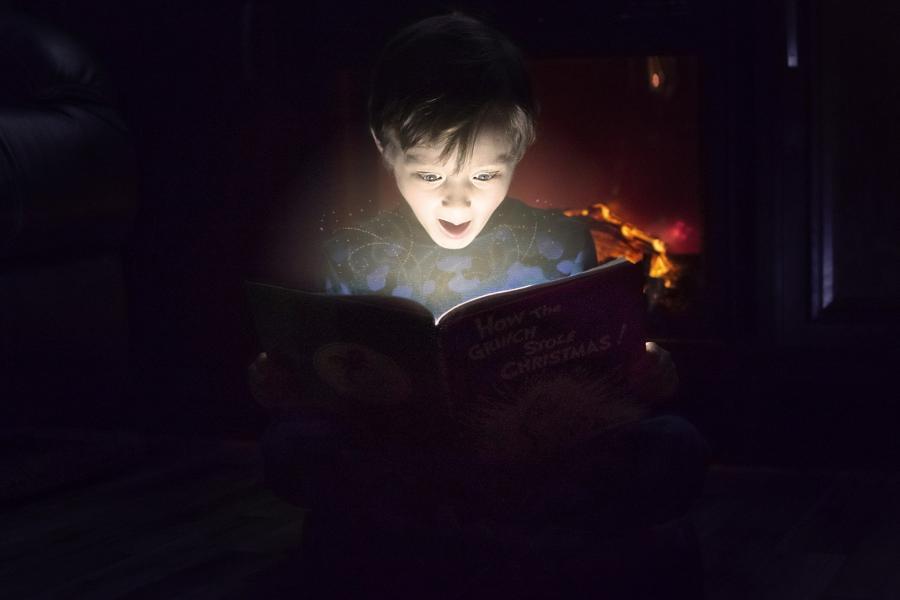 En dreng der sidder i mørke og læse i en bog der er oplyst