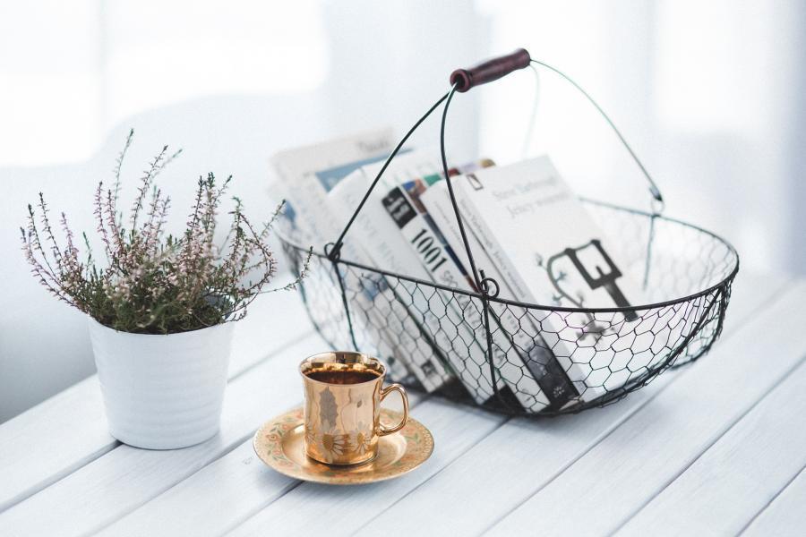 Et bord hvorpå man kan se en plante, en kop og en kurv med bøger i.